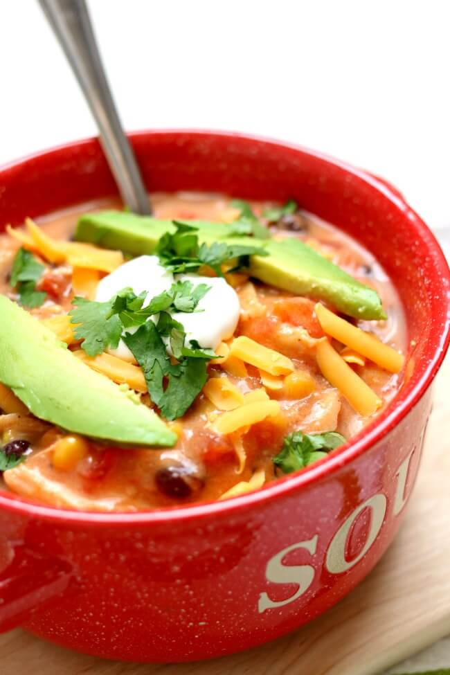 Slow Cooker Creamy Tortilla Soup is a dump and go crockpot recipe that tastes amazing! We love topping ours with avocado, tortilla chips, cheese and sour cream.