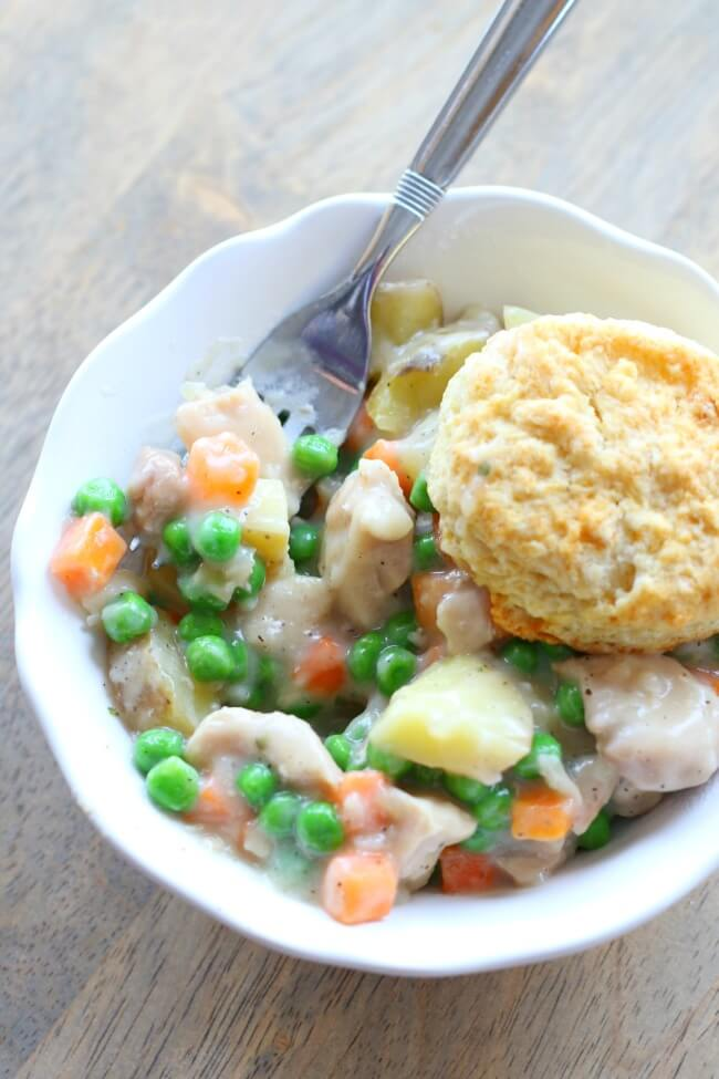 Easy and delicious recipe for chicken pot pie in the crockpot--peas, carrots, potatoes and chicken with a cream sauce and flaky biscuits