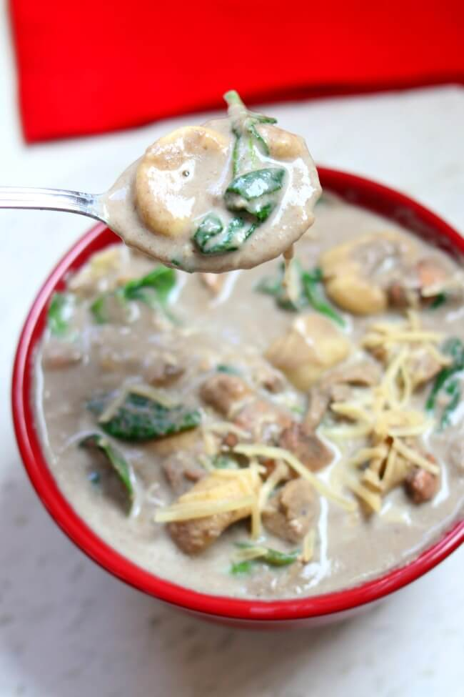 Slow Cooker Chicken Mushroom Tortellini Soup: a creamy, comforting cream of mushroom soup with tender bites of chicken, cheesy tortellini, fresh spinach and topped with freshly grated Parmesan cheese.