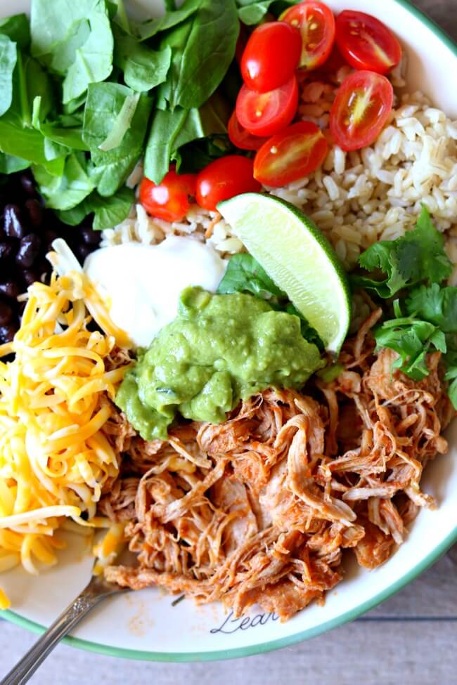 Slow Cooker or Instant Pot Savory Pork Burrito Bowls–perfectly tender and shreddable 5 ingredient pork is cooked quickly in your Instant Pot and then served with rice, guacamole, black beans, sour cream and more of your favorite toppings.