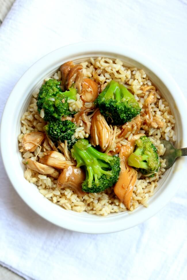 Instant Pot Chicken Broccoli Rice Bowl--brown rice is topped with a savory asian-inspired sauce, tender pieces of chicken and bright green, barely cooked broccoli florets.