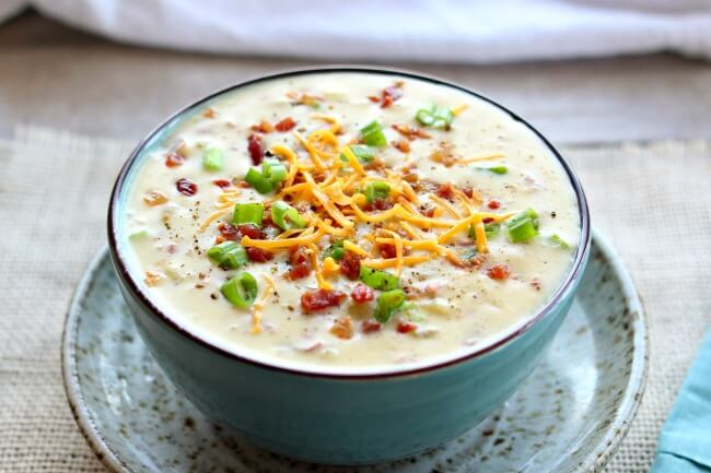 Instant Pot Loaded Baked Potato Soup--everything you love about baked potatoes in soup form...cheese, bacon, sour cream, green onions and potatoes. Basically a cheesy potato soup recipe that you can make in your electric pressure cooker.