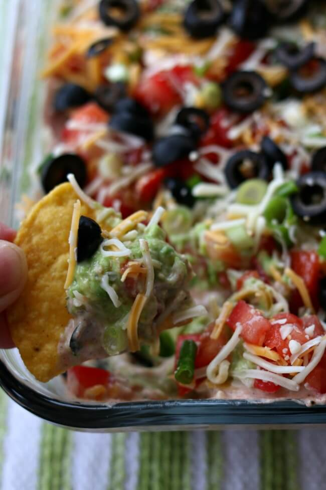 7 Layer Dip--this is the best 7 layer dip I have ever eaten! It starts with a layer of perfectly seasoned homemade refried beans (which you can make in the Instant Pot or slow cooker), then a layer of sour cream mixed with taco seasoning and salsa, next a layer of smashed avocados seasoned with lime juice and finally it's topped with diced tomatoes, green onions, cheese and olives. Every layer comes together in perfect harmony on top of a tortilla chip and popped into your mouth.