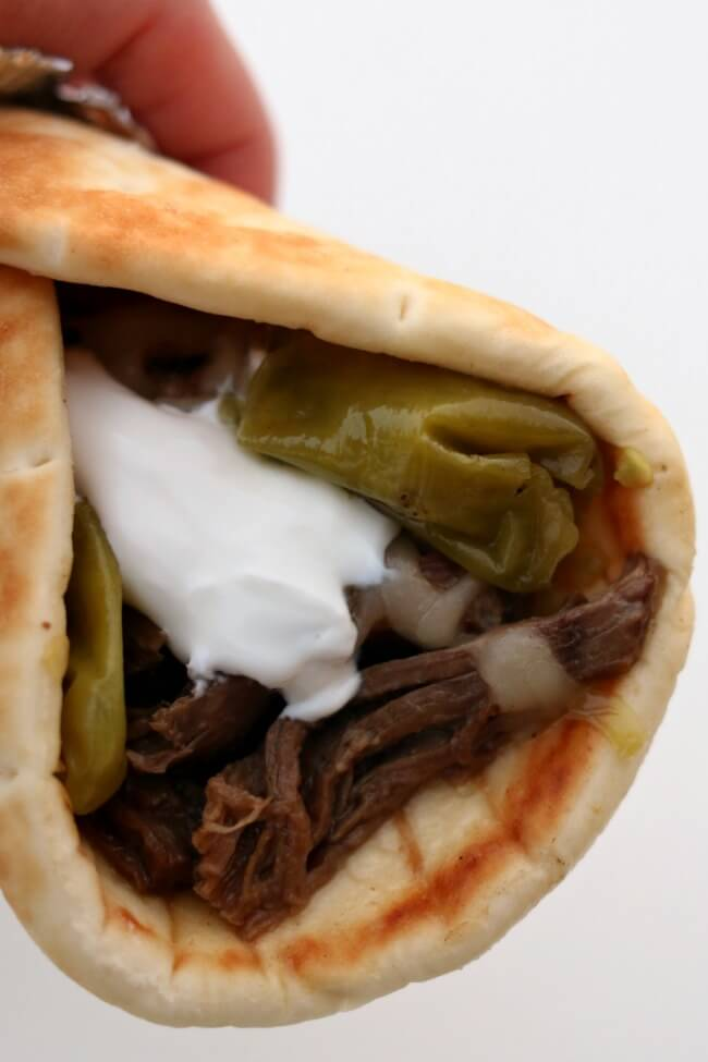 Instant Pot Mississippi Roast Gyros--tender shredded beef that has been cooked in pepperoncini juice is piled into a soft pita and then topped with monterey jack cheese and a dollop of sour cream.