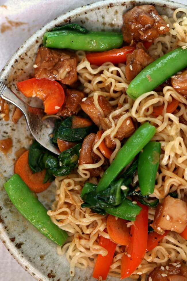 Slow Cooker Honey Bourbon Chicken Noodle Bowls--tender bites of chicken thighs are cooked in a honey-soy-garlic sauce and then served over ramen-style noodles with stir fried vegetables. This chicken is just as good as what you'd order in a restaurant.