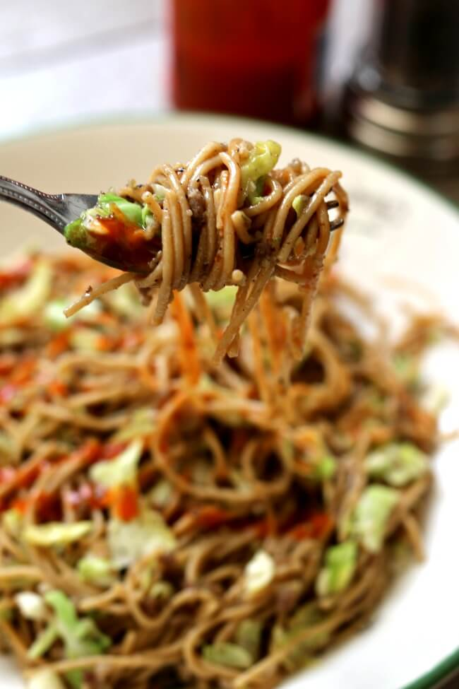 Instant Pot Pepper Noodles--thin spaghetti is tossed with tamari, pepper, ground sausage and shredded cabbage for an easy one pot meal with a lot of flare. To give it some extra kick drizzle sriracha on top of the noodles.