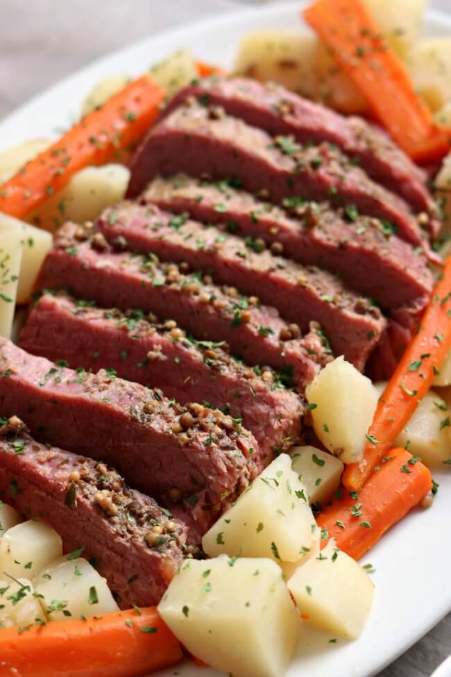 Instant Pot Corned Beef Dinner with Mustard Sauce--a super easy (and delicious) method for making corned beef! Tender corned beef is sliced and served alongside carrots and potatoes (and if you want, cabbage). Top your corned beef with a tangy sauce made of sour cream, dijon mustard and garlic. A perfect dinner for St Patrick's Day (or any other day).