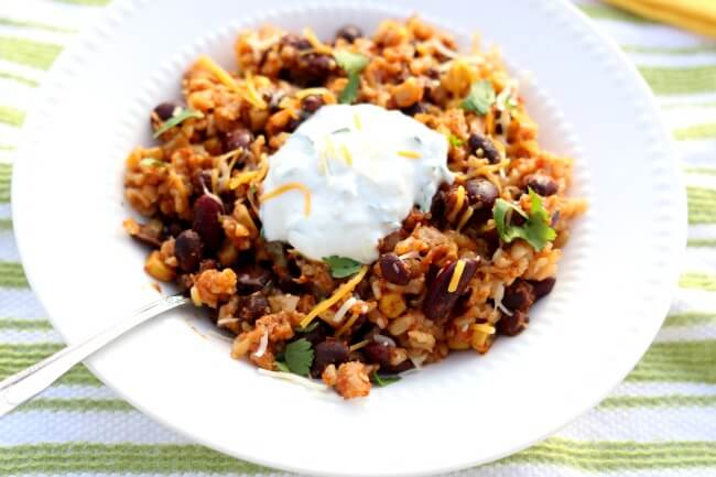 Instant Pot Santa Fe Beans and Rice--brown rice, kidney beans and black beans are simmered with salsa, corn and seasonings in your electric pressure cooker. Serve with garlic lime sour cream and grated cheddar cheese on top. Serve as a meatless meal or add in chicken for some extra protein. We love this easy and healthy, family friendly meal.