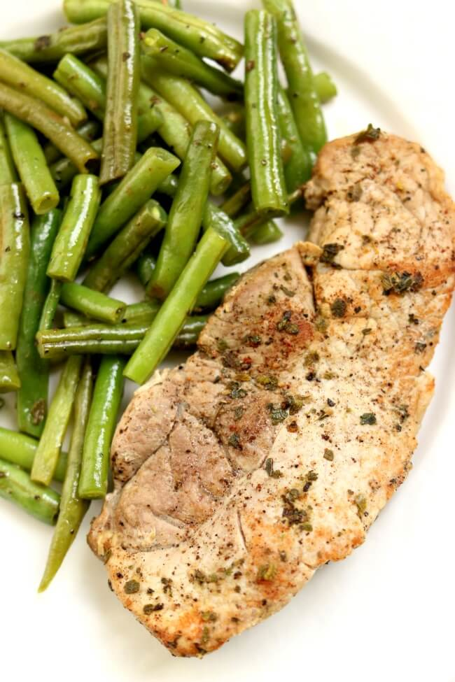 Instant Pot Garlic Herb Pork Chops and Green Beans--this one pot meal can be made in minutes. The pork chops and green beans are full of rich buttery herb flavors. Serve as is for a low-carb meal or serve with your favorite starch (potatoes, rice or noodles).