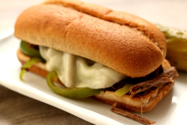 Instant Pot/Slow Cooker Philly Cheesesteak Sandwiches--tender shredded beef and green peppers are cooked in your electric pressure cooker or slow cooker. The beef is piled onto toasted buns that are slathered with mustard and mayo and then topped with melty cheese.