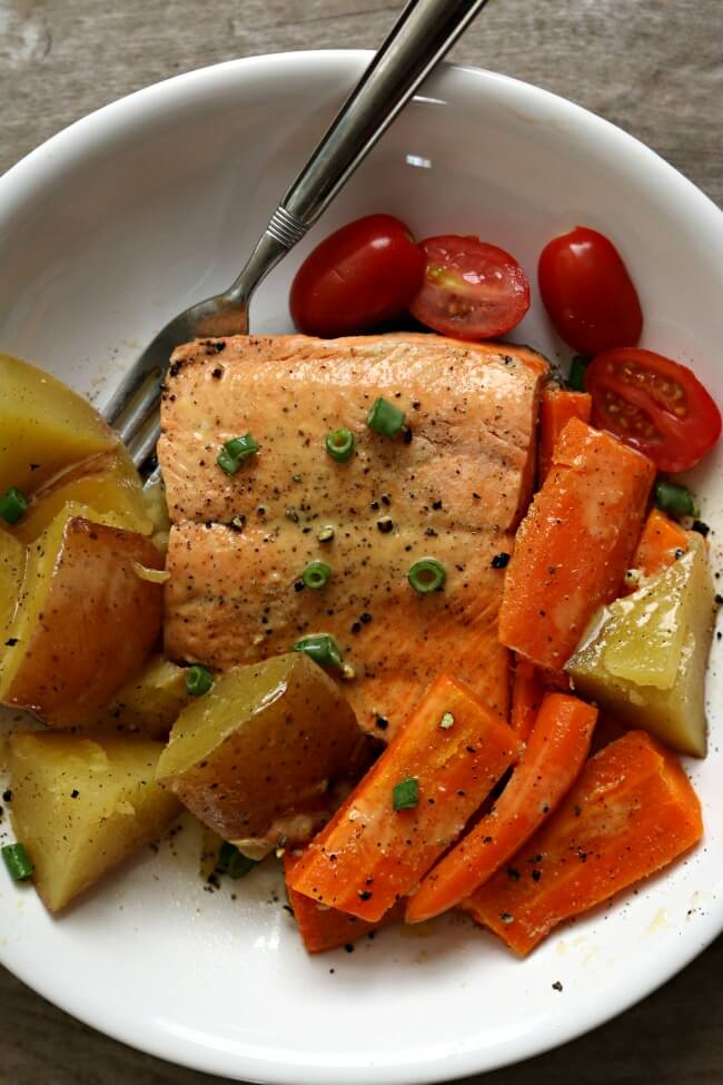 Instant Pot Lemon Butter Garlic Salmon with Homestyle Vegetables--flaky wild Alaska salmon is steamed on the top of red potatoes and carrotsin your electric pressure cooker and topped with garlic, fresh lemon juice and butter. A one pot meal that is healthy and delicious!