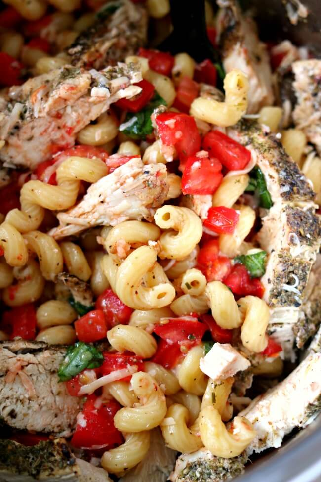 Instant Pot Bruschetta Chicken Pasta--the most tender bites of well seasoned chicken stirred in with curly al dente pasta, tomatoes, olive oil, garlic and fresh basil. A fresh and bright summer pasta dish that takes minutes to make in your electric pressure cooker.