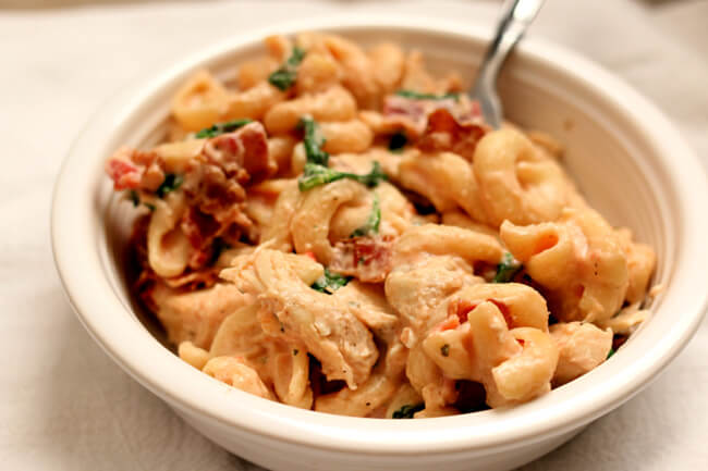 Instant Pot Chicken Bacon Ranch Pasta--curly pasta is enveloped in a creamy sauce with tender bites of chicken, crispy bites of bacon and a green pop of color from spinach or broccoli. A one pot pasta dish that rivals anything you can order at a restaurant.