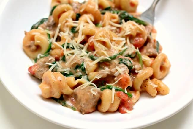 Instant Pot Creamy Sausage Parmesan Pasta--curly al dente pasta is enveloped in a creamy sauce with bites of baby spinach, petite tomatoes and Italian sausage.