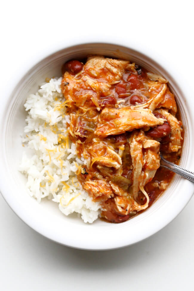 Instant Pot Southwest Shredded Chicken Bowls--a stew that is bursting with flavor but not too spicy. It has tender shredded chicken, pinto beans, fire roasted tomatoes, green chiles and taco seasoning. Serve this stew over rice or plain for an easy weeknight dinner.