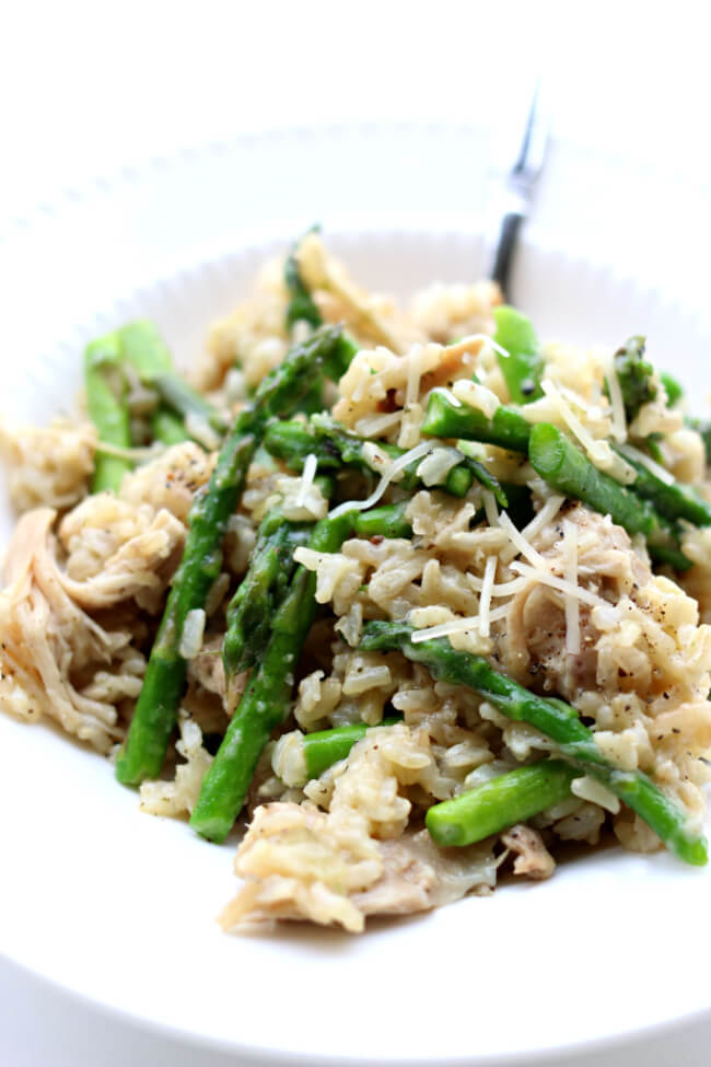 Instant Pot Garlic Rice and Chicken--brown rice is cooked with fresh garlic and tender bites of chicken. Parmesan cheese and asparagus (or broccoli) are stirred in to make a perfect one pot meal.