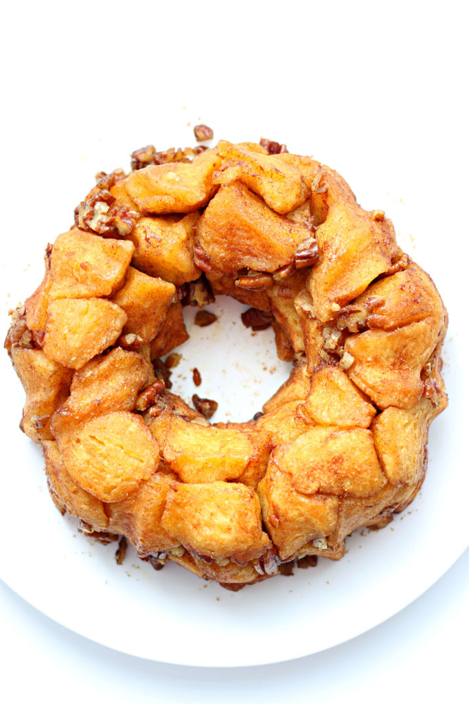 A white plate with a bundt cake shape of pull apart biscuit monkey bread on top