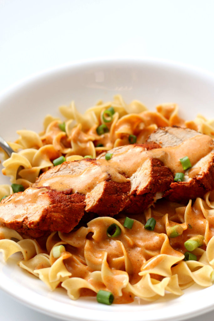 A white bowl with eggs noodles, sliced pork tenderloin and a paprika creamy sauce over the top