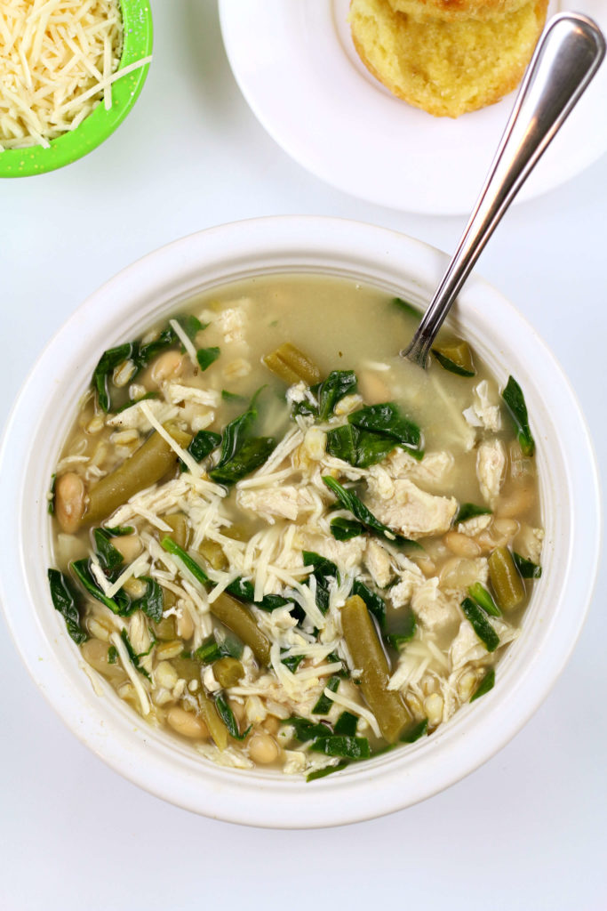 Green and white soup with white bowl and a spoon