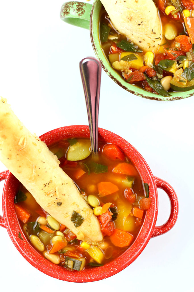 vegetable soup with breadsticks in it