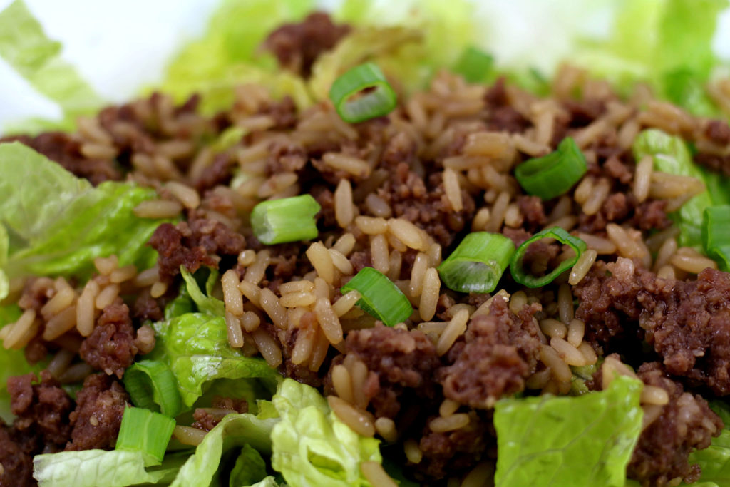 chopped romaine lettuce on a white plate with ground meat and rice on top