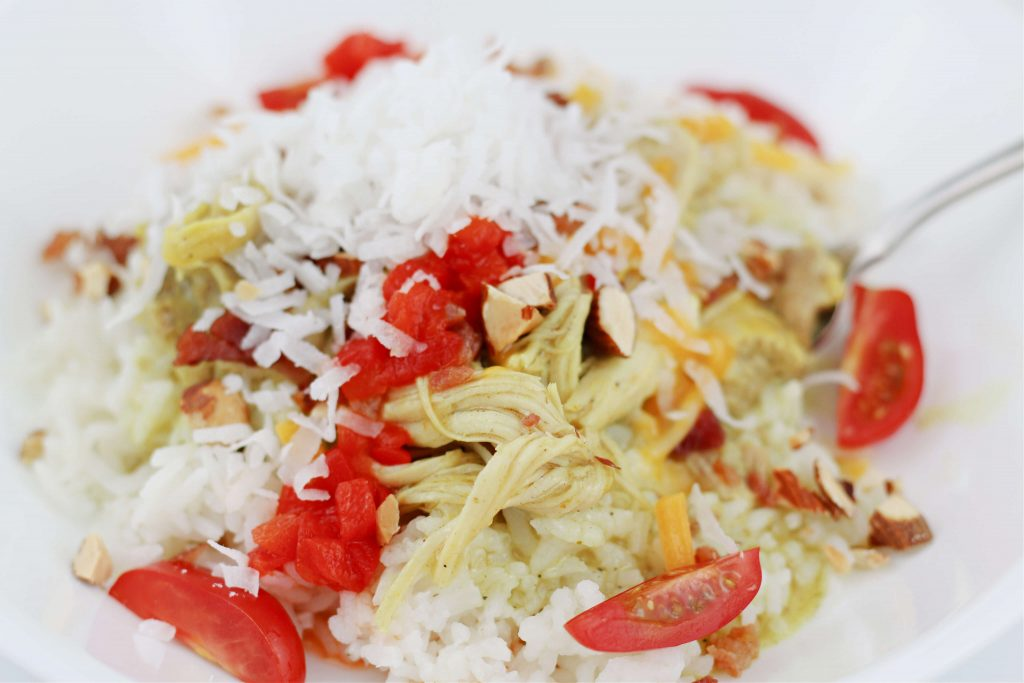 rice with chicken, almonds, cheese, tomatoes and coconut on top