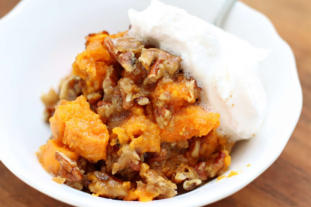 Sweet potato praline casserole in a bowl with whipped cream