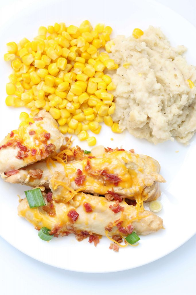 chicken with corn and mashed potatoes on a white place